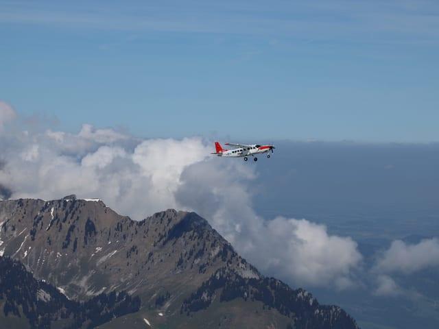 An einem Bergrücken bilden sich Wolken, ein Motorflugzeug fliegt darüber hinweg.