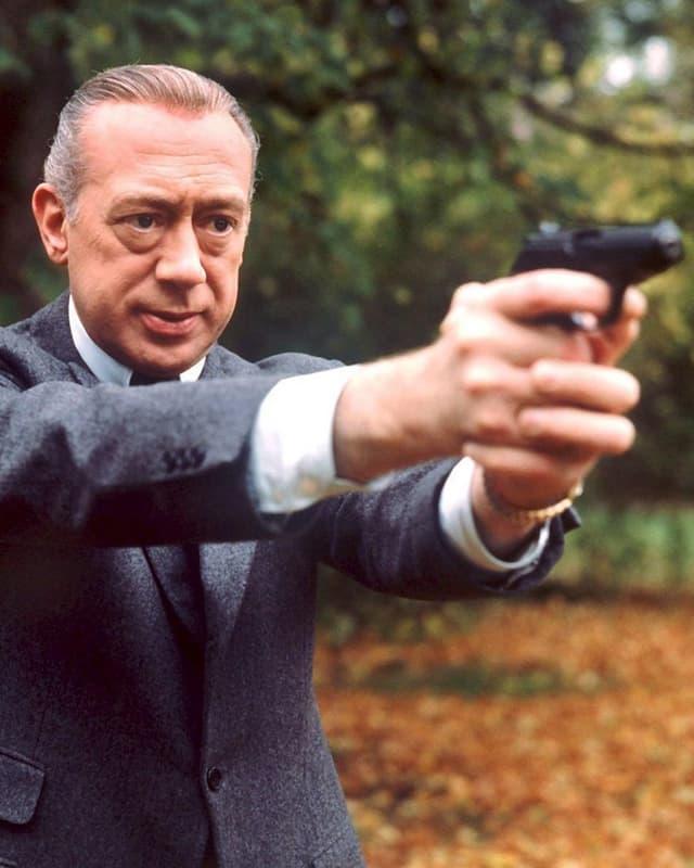 Horst Tappert zielt als Inspektor Stephan Derrick Richtung Kamera.
