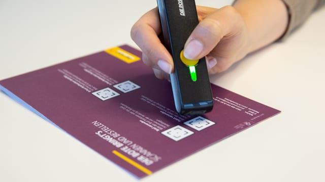 Hand hält stiftähnliches Gerät mit gelbem Knopf.