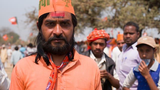 Im Vordergrund junger indischer Mann, orange gekleidet. Im Hintergrund andere junge Männer