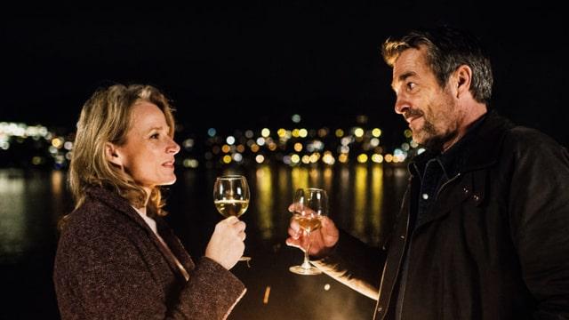 Eveline Gasser (Brigitte Beyeler) und Kommissar Reto Flückiger (Stefan Gubser) mit Weingläsern vor romantisch verschwommener Kulisse im Dunkeln. ee zum ersten Jahrestag.