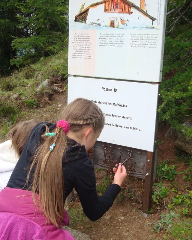 Zwei Mädchen knien bei einem Spielposten auf der Wanderung.