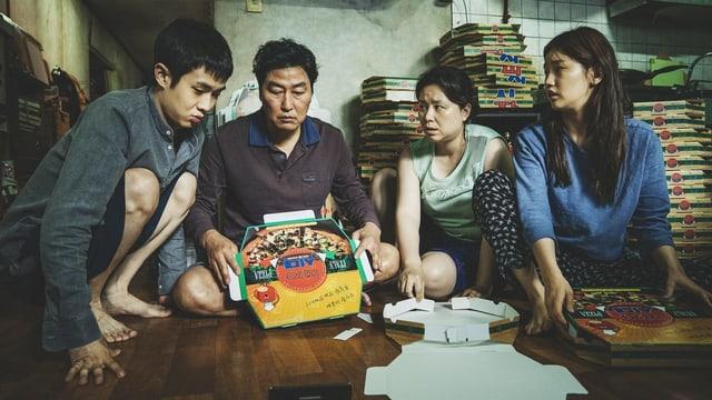 Eine Familie mit Tochter und Sohn blickt auf eine Kartonbox.