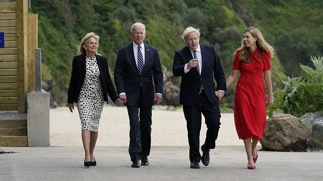 Biden und Johnson laufen zusammen mit ihren Ehefrauen in der Nähe des Meeres entlang.