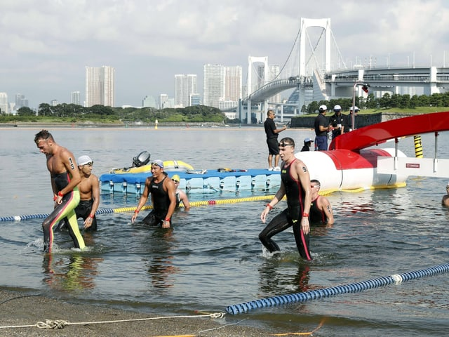 Swimmers come out of the water in Tokyo