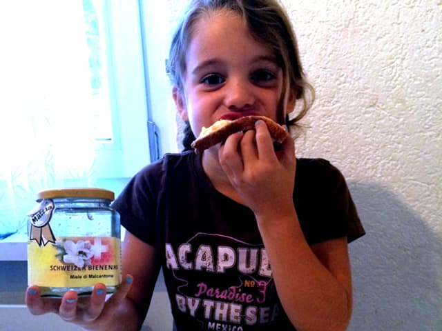 Lena beisst ins Honigbrot.