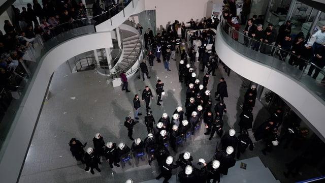 Eingangshalle von oben fotografiert, dort stehen dutzende Polizisten mit weissen Helmen und Schildern.