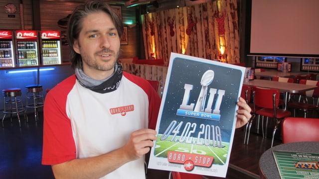 Tobias Hubacher mit einem Plakat im Road Stop Cafe
