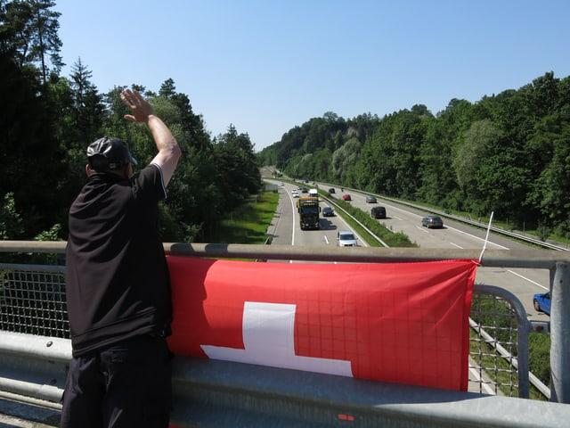 Zu sehen ist ein Mann der winkt, vor ihm hängt eine Schweizer Fahne.