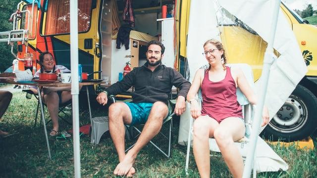 Zwei Menschen sitzen vor ihrem Camper