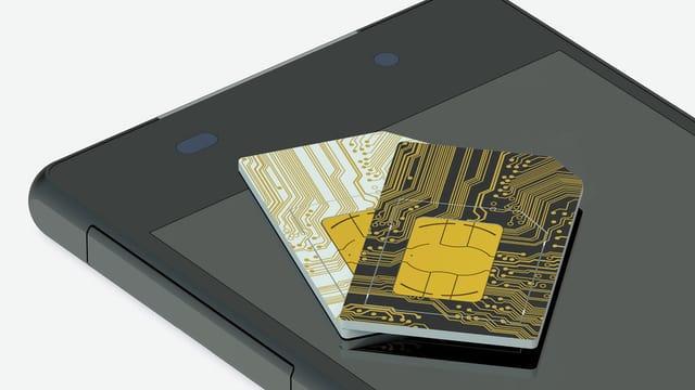 Zwei SIM-Karten liegen auf einem Handy.
