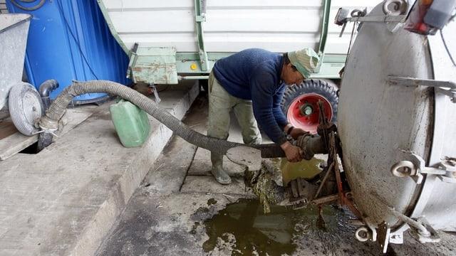 Ein Landwirt pumpt Jauche in sein Güllenfass.