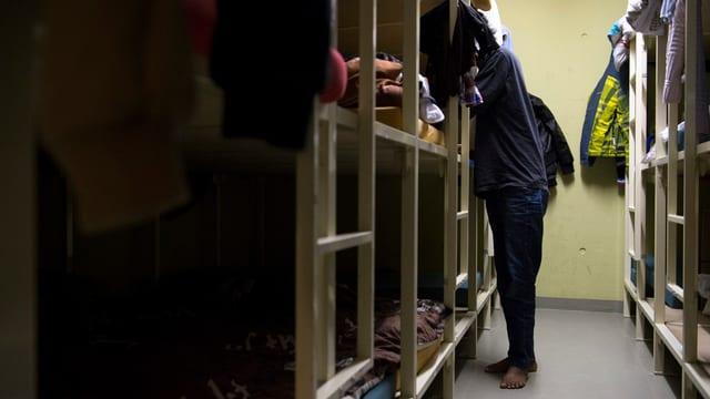 Ein Mann steht zwischen zwei Reihen Kajütenbetten, Kopf versteckt.