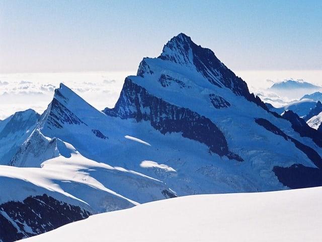 verschneiter Berg mit Nebelmeer dahinter