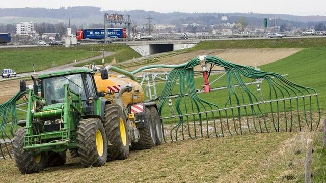 Ein Traktor bringt mit Schleppschläuchen Jauche aufs Feld.