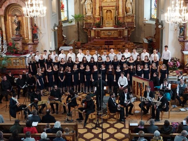 Einn Chor und verschiedene Musikerinnen und Musiker während eines Kirchenkonzerts.
