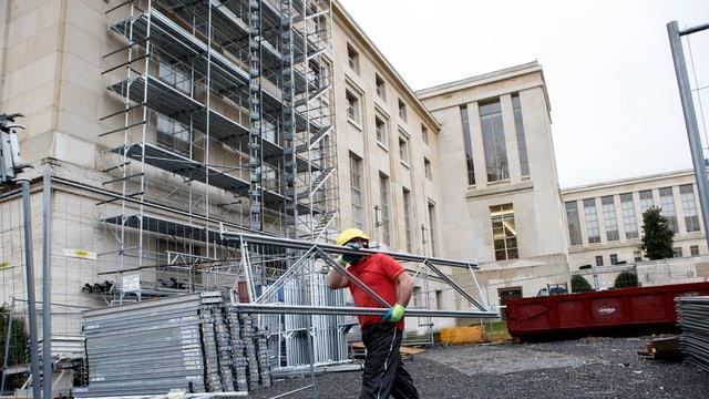 Bauarbeiter vor dem eingerüsteten UNO-Hauptsitz in Genf