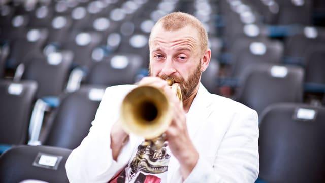 Mann mit weissem Sacko spielt Trompete.