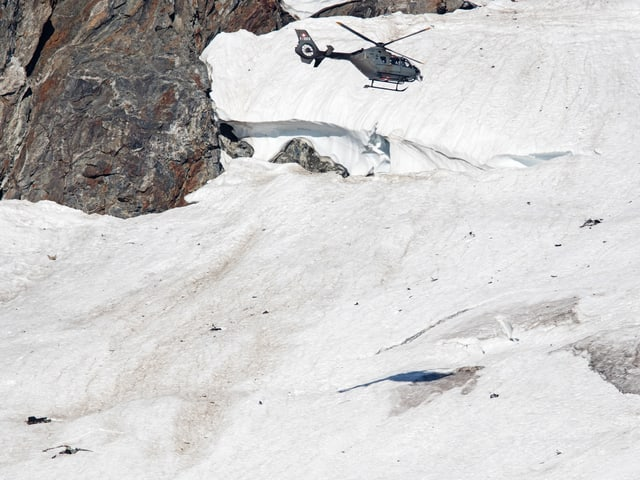 Armeehelikopter überfliegt kleinere Flugzeugtrümmer am Fuss einer Felswand