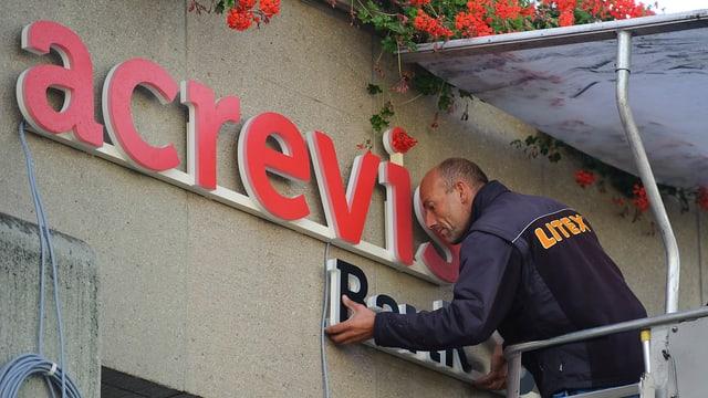 Ein Mann montiert das Logo der fusionierten Acrevis-Bank am Gebäude in St. Gallen.