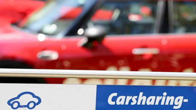 Carsharing-Schild vor einem roten Wagen.
