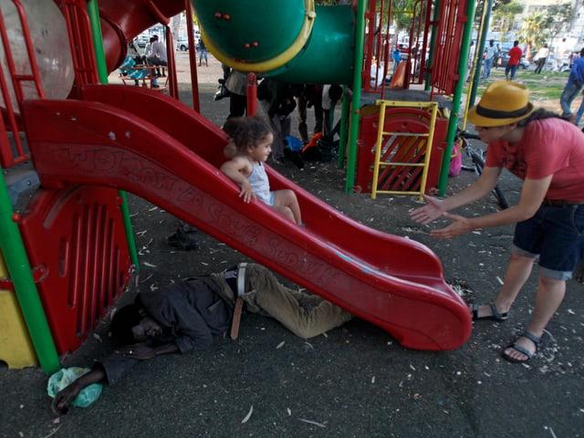 Eine Frau steht am Ende einer Rutschbahn, auf der ein kleines Mädchen runter rutscht. Unter der Rutschbahn liegt ein afrikanischer Flüchtling.