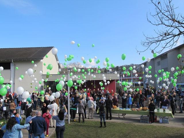 Menschen lassen grüne und weisse Luftballons steigen.