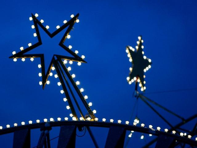 Weihnachtsbeleuchtung in Form von zwei Sternen vor blauem Himmel.
