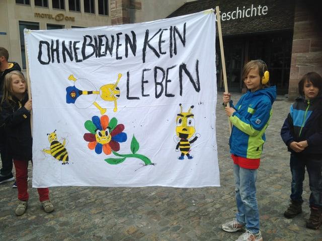 Drei Knaben mit einem Transparent mit Bienen.
