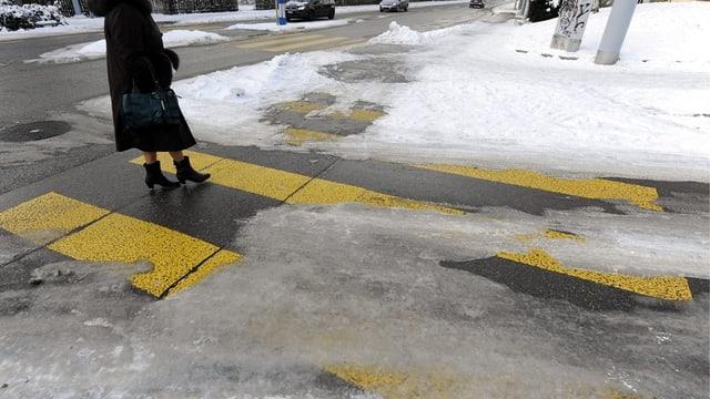 Frau überquert einen Fussgängerstreifen, der Schnee bedeckt ist.