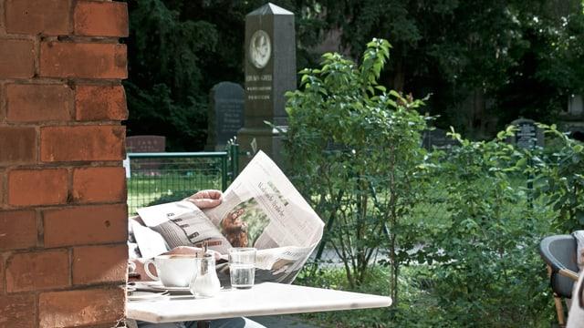 Zeitung und Kaffeetasse im Vordergrund, Grabstein im Hintergrund.