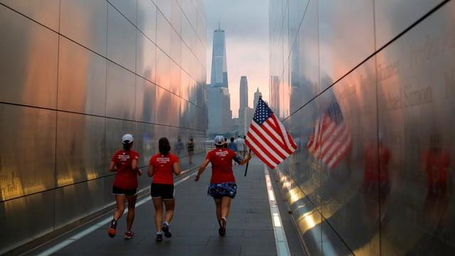 Frauen, die mit einer amerikanischen Flagge durch das Memorial von 9/11 rennen.