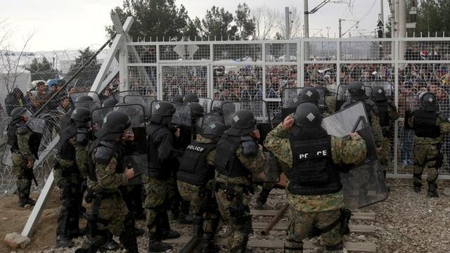 Die mazedonische Polizei, geschützt durch Helme, Westen und Schutzschilder steht zahlreichen Flüchtlingen am Grenzzaun gegenüber.