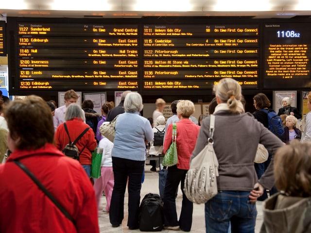Viele Menschen stehen mit Blick auf eine orange leuchtende, elektronische Anzeigetafel, in einer Bahnhofshalle und warten..