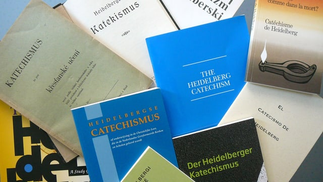 Mehrere Ausgaben der Heidelberger Katechismus, deutsche und fremdsprachige, liegen auf einem Tisch angeordnet.