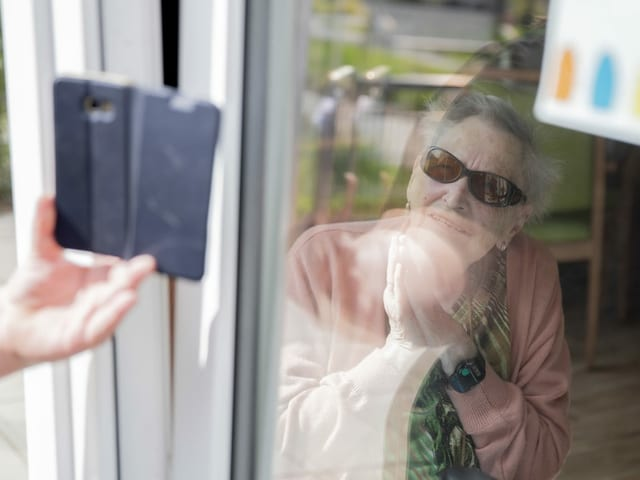 Seniorin sitzt zuhause