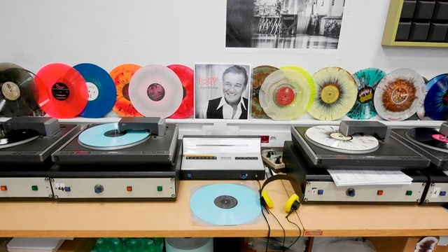 Vier Plattenspieler spielen fertige Schallplatten ab.
