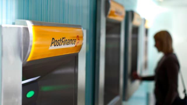 Eine Frau vor einem Bankomat der PostFinance