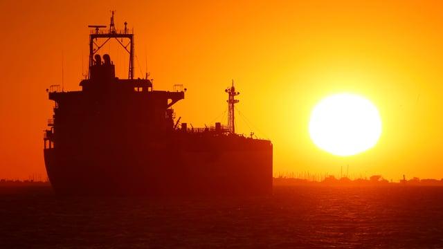 Ein Öltanker auf dem Meer bei Sonnenuntergang.
