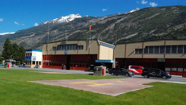 Im Vordergrund Helikopter-Hangars, im Hintergrund Berge.