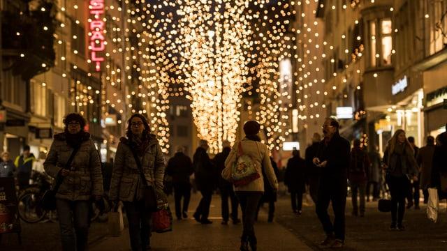 Menschen in einer Strasse mit Weihnachtsbeleuchtung.