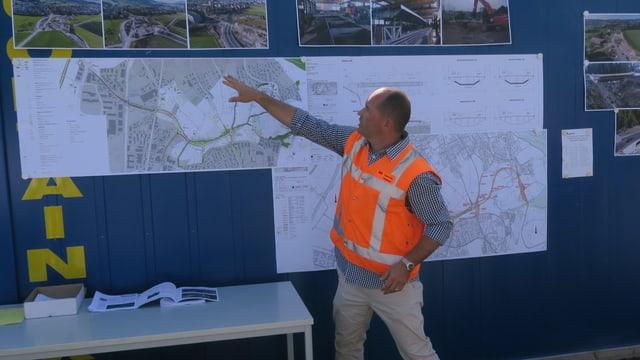 Ein Mann in oranger Weste erklärt einen Plan.