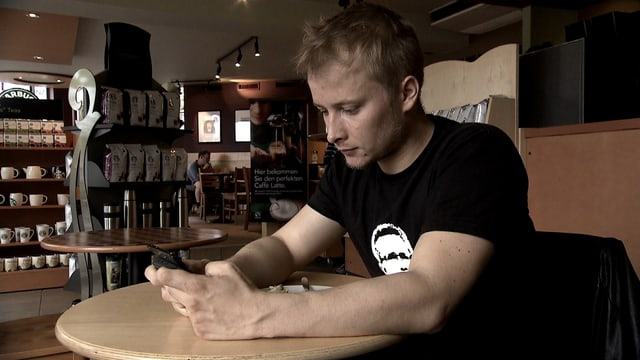 Peponi in einem Restaurant mit seinem Handy in der Hand.