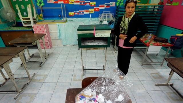 Eine thailändische Frau steht alleine in einem Wahllokal.