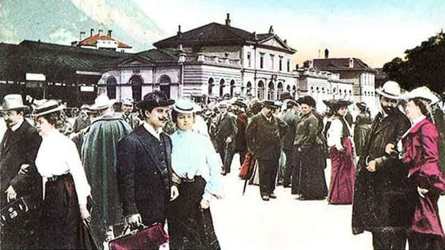 Männer und Frauen auf einem Bahnhofplatz vor 100 Jahren.