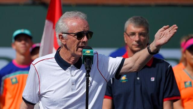 Raymond Moore spricht in Indian Wells in eine Mikrophon und zeigt mit der linken Hand in eine Richtung. Er trägt eine dunkle Sonnebrille.