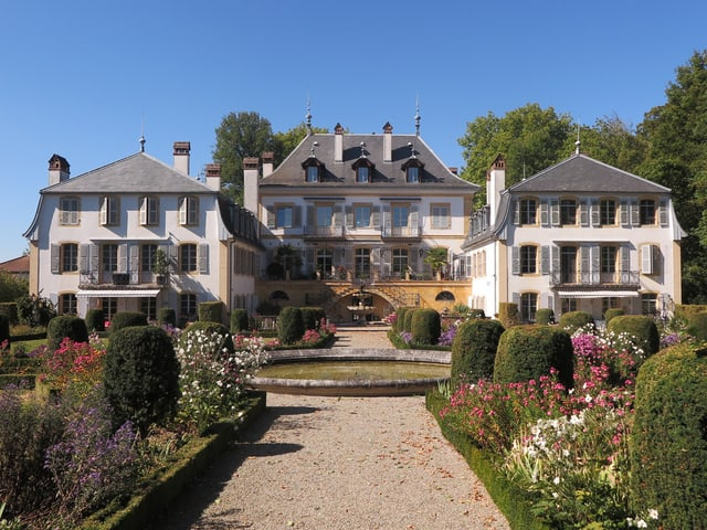 Blick auf das Schloss, davor eine üppige Gartenanlage