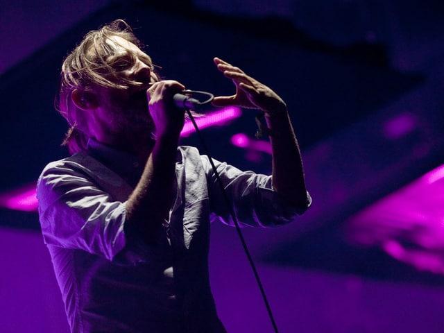 Der Sänger Thom Yorke singt in ein Mikrofon an einem Konzert.