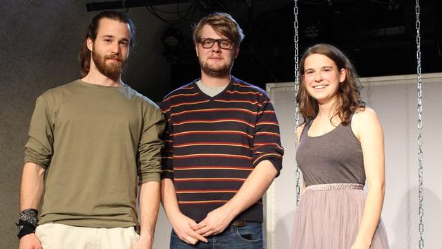 Drei Menschen stehen auf einer Bühne.