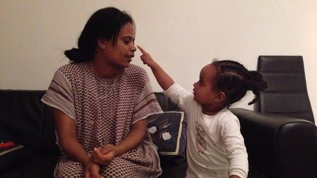 Ein kleines Mädchen deutet mit dem Finger auf die Nase der Mutter, die neben ihr auf dem Sofa sitzt.